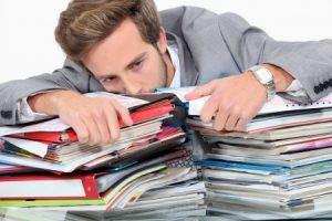 drowning in stacks of paperwork
