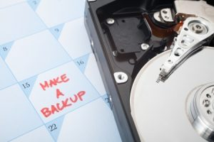 make a backup of hard disk reminder. calendar with text and hard drive. selective focused on text backup and magnetic head.