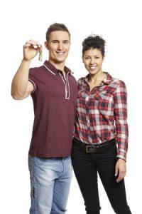 young couple holding set of house keys on white background smiling