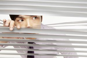 businessman peeking through window blinds