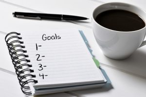 closeup of a notebook with a blank list of goals and a cup of coffee on a white wooden table