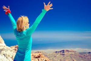 woman successful hiking climbing in inspirational mountains landscape, beautiful view and ocean. female hiker with arms up outstretched on mountain top.